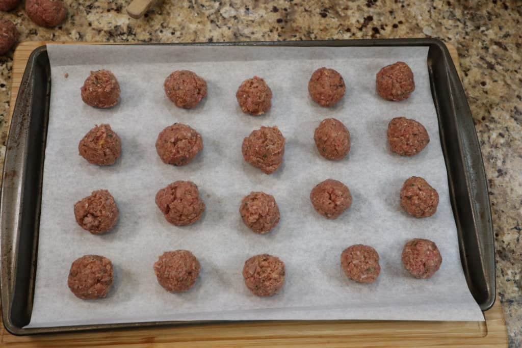 Uncooked meatballs on a baking sheet