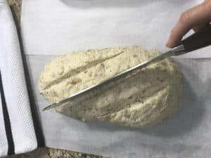 cutting top of loaf of bread dough