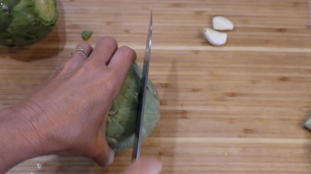 cutting the top off of an artichoke